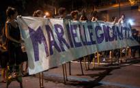 """A group of women on stilts hold a banner reading """"Giant Marielle"""" during a protest against the murder of Brazilian councilwoman and activist Marielle Franco in Rio de Janeiro, Brazil on 15 March, 2018. Picture: AFP."""