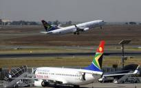 FILE: A South African airways flight takes off as another one is parked in a bay on the tarmac at the Johannesburg OR Tambo International airport in Johannesburg, South Africa. Picture: AFP.