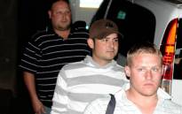 FILE: Two of the 'Waterkloof Four' Reinach Tiedt, front, and Frikkie du Preez, 2nd from front, are escorted by a police officer to a car to take them to prison to begin their 12-year sentence. Picture: Sapa.