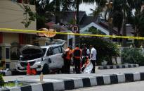 Indonesian policemen examine a car used by attackers outside the police headquarter in Pekanbaru, Riau following attacks on 16 May, 2018. Picture: AFP