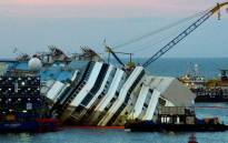 A picture taken on September 16, 2013 shows the wreck of Italy's Costa Concordia cruise ship which begins to emerge from water near the harbour of Giglio Porto. Salvage operators in Italy lifted the Costa Concordia cruise ship upright from its watery grave off the island of Giglio on September 17 in the biggest ever project of its kind. Picture: AFP