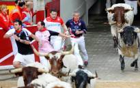 FILE: Participants run in front of Torrestrella's bulls during the first bull-run of the San Fermin Festival on 7 July in Pamplona, northern Spain. Picture: AFP.
