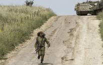 An Israeli soldier runs to direct a M113 armored personal vehicle near the Syrian border in the Israel-annexed Golan Heights on 10 May 2018. Picture: AFP