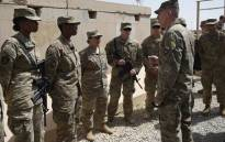 The US commander in Afghanistan John Nicholson (R) talks with soldiers in the Afghan province of Helmand on 29 April 2017. Picture: AFP.