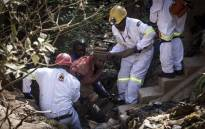 FILE: The mine rescue team helps pull an injured illegal miner out of the disused Langlaagte Gold Mine shaft entrance. Picture: AFP.