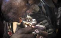 A heroin addict smokes, or chases, heroin off a piece of aluminium foil in Woodstock, Cape Town. Picture: Thomas Holder/EWN