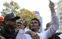 This file photo taken on February 18, 2014 shows Leopoldo Lopez (R), an ardent opponent of Venezuela's socialist government facing an arrest warrant, being escorted by the National Guard after turning himself in, during a demonstration in Caracas on February 18, 2014. Juan BARRETO / AFP