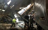 FILE: Train personnel survey the NJ Transit train that crashed in to the platform at the Hoboken Terminal 29 September 2016 in Hoboken, New Jersey. Picture: AFP.