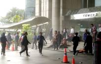 This photo received from Amailia Putri Hasniawati via WhatsApp shows people running for cover at the entrance of Indonesia's stock exchange in Jakarta after an internal balcony collapsed on 15 January, 2018. Picture: AFP