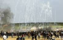Palestinian protesters run for cover from tear gas fired by Israeli security forces during clashes following a demonstration commemorating Land Day, near the border with Israel, east of Gaza City, on 30 March 2018. Picture: AFP.