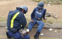 FILE: A police officer helps his fellow officer after being injured during a violent protest. Picture: Louise McAuliffe/EWN