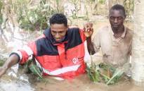 A Kenya Red Cross worker helps a man through a flooded field. Picture: @KenyaRedCross/Twitter