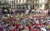 People stand next to flowers, candles and other items set up on the Las Ramblas boulevard in Barcelona as they pay tribute to the victims of the Barcelona attack, three days after a van ploughed into the crowd, killing 13 persons and injuring over 100 on 20 August, 2017. Picture: AFP.