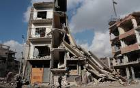 FILE: Syrians walk past a destroyed building in the rebel-held town of Douma, on the eastern outskirts of Damascus, on December 30, 2016. Picture: AFP.