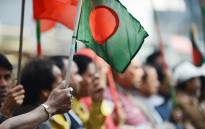 FILE: A supporter of Bangladeshi Prime Minister Sheikh Hasina holds a national flag during a rally in front of her political party's headquarters in Dhaka on January 4, 2014. Picture: AFP.
