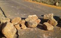 Rocks blockade a road during a protest. Picture: @SAPoliceService/Twitter