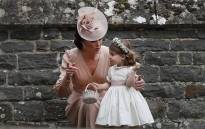 FILE: Britain's Catherine, Duchess of Cambridge, speaks to her daughter Princess Charlotte at the wedding of her sister Pippa Middleton on 20 May 2017. Picture: AFP.