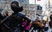 'The Fearless Girl' statue facing the iconic Wall Street charging bull statue as part of a campaign to push companies to add women on their boards on 8 March 2017 in Lower Manhattan, New York. Picture: AFP.