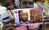 FILE: A supporter of Ivory Coast's former president Laurent Gbagbo holds a flyer picturing Gbagbo. Picture: AFP.