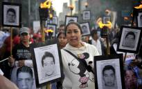 FILE: The parents of 43 missing students from Ayotzinapa teachers school hold their portraits and torches during a march in 2016. Picture: AFP.