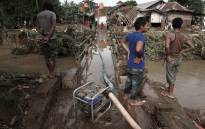 FILE: Villagers look on after waters receded following floods in Indonesia. Picture: AFP