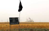 FILE: An Islamic State group (IS) flag and banner in Iraq. Picture: AFP.