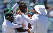 South African bowler Kagiso Rabada is embraced by teammates after he had taken his fifth wicket on day five of the first Test cricket match between Australia and South Africa in Perth on 7 November, 2016. Picture: AFP.