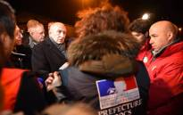 French Interior Minister Gerard Collomb (L) meets with DDCS personnel on 2 February 2018 in Calais, northern France, following a large brawl between a hundred migrants which resulted in several injuries. Picture: AFP