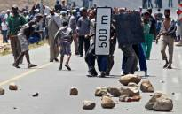Striking farmworkers hurl rocks at police during a protest for better wages in De Doorns in the Western Cape, Thursday, 10 January 2013. Picture: Nardus Engelbrecht/SAPA.