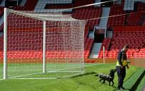 A sniffer dog searches behind one of the goals at Old Trafford stadium in Manchester, north west England, on May 15, 2016, after the English Premier League football match between Manchester United and Bournemouth was abandoned. Police ordered Manchester United to abandon their final Premier League game of the season against Bournemouth on Sunday after a suspicious package was discovered at Old Trafford. Picture: AFP.