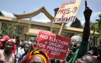 Supporters of President Uhuru Kenyatta-led Jubilee Alliance shout slogans during a demonstration on September 19, 2017 outside the Supreme court of Kenya in Nairobi where a fresh petition was filed against it's judges. Picture: AFP.