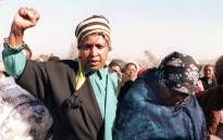 "FILE: Winnie Madikizela-Mandela (l), raises a clenched fist on 27 July 1987 during the funeral of Sello Motau, senior member of the ""Umkhonto We Sizwe"", the ANC military wing, who was gunned down in Swaziland 9 July 1987. Picture: AFP"