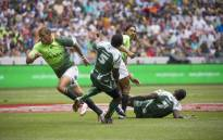 Juan de Jongh races past Zimbabwe's Stephan Hundaza during the Blitzboks' opening game on the first day of the Cape Town Sevens tournament on 12 December 2015. Picture: Aletta Harrison/EWN