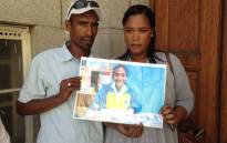 Chantel and Joseph Boltman hold a photo of their son outside court. Picture: Lauren Isaacs/EWN