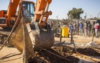 Police clear a pit and structure used for sifting gold concentrate from illegal mines during an operation in Matholeville aimed at removing illegal mining operations on 26 July 2017. Picture: Thomas Holder/EWN