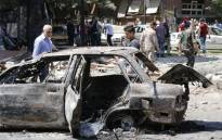 Syrian men stand next to a charred vehicle as they inspect the damage at the site of a suicide bomb attack in the capital Damascus' eastern Tahrir Square district, on July 2, 2017. Syrian state television reported that security forces had intercepted three suicide car bombers on their way into the city, killing two, but the third managed to reach the eastern Tahrir Square district. The attacker was surrounded but was able to detonate a bomb, killing a number of people and wounding several more, it reported. Picture: AFP.