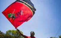 An Economic Freedom Fighters (EFF) member waves the party's flag outside the Israel Embassy in Pretoria during a free Palestine protest. Picture: Thomas Holder/EWN.