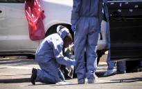 "A forensic team member combs the scene where Lebanese drug dealer Sam ""Black"" Issa was gunned down in a drive-by shooting in Bedfordview on 12 October 2013. Picture: Reinart Toerien/EWN"