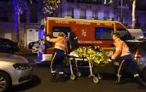 FILE: Rescuers evacuate an injured person on Boulevard des Filles du Calvaire, close to the Bataclan concert hall in central Paris, early on 14 November 2015. Picture: AFP.