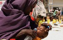 FILE: An internally displaced woman from southern Somalia gives water to her daughter at a distribution centre in Mogadishu. Picture: AFP.