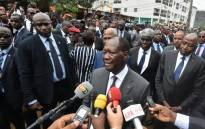FILE: Ivorian President Alassane Ouattara (C) answers journalists' questions during his visit at the flood-prone zones on 21 June 2018 at Rivera, at the Cocody district of Abidjan. Picture: AFP