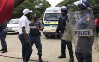 A demonstrator seen with police in the North West after Nehawu clashed with ANCYL members over calls for Premier Supra Mahumapelo to step down. Picture: Masechaba Sefularo/EWN.