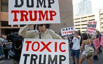 Protesters outside the Phoenix Convention Center hold up anti-President Donald Trump signs during a rally held by Trump on August 22, 2017 in Phoenix, Arizona. Picture: AFP