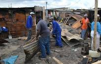 FILE: Men clear debris of a shack fire. Photo: Aletta Gardner/EWN