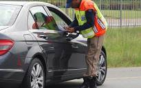 FILE: A traffic officer stops a motorist during a roadblock. Picture: EWN.