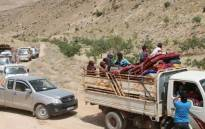 Syrian refugees ride vehicles in the Lebanese eastern border town of Arsal as they head towards the Syrian region of Qalamoun on 12 July 2017 as part of a deal that was negotiated by Syrian rebels in the camps and Lebanon's Hezbollah group. Picture: AFP.