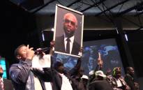 Mourners hold a placard with Mduduzi 'Mandoza' Tshabalala's face during the Kwaito legend's funeral at Grace bible Church in Soweto on 23 September 2016. Picture: Katleho Sekhotho/EWN.