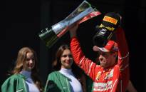 Ferrari's German driver Sebastian Vettel displays his trophy on the podium after winning the Brazilian Formula One Grand Prix, at the Interlagos circuit in Sao Paulo, Brazil, on 12 November 2017. Picture: AFP
