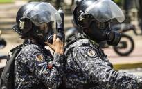 FILE: Police officers ride on a motorbike as anti-government activists demonstrate against Venezuelan President Nicolas Maduro in Caracas on 8 August 2017. Picture: AFP.