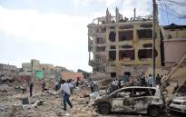 People react and walk among rubbles following an attack outside a hotel on 25 January 2017, in Mogadishu. Picture: AFP.